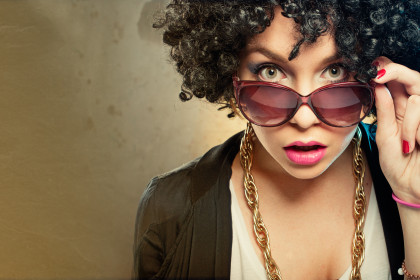 Girl with afro haircut, surprised, pink lipstick, golden necklace, retro sun glasses, copy space to the left of the subject. retro colors.